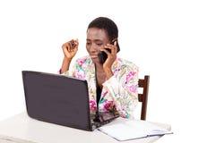 Jeune femme d'affaires à l'aide d'un téléphone portable et d'un ordinateur portable image libre de droits