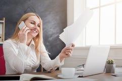 Jeune femme d'affaires élégante tenant des documents et parlant au téléphone Photo stock
