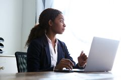 Jeune femme d'affaires africaine s'asseyant à son bureau avec un ordinateur portable photos libres de droits