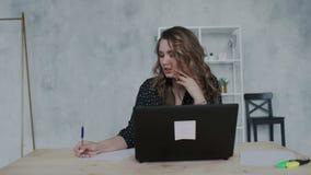 Jeune femme d'affaires agréable avec l'ordinateur portable invitant le téléphone au bureau et écrivant des notes dans le papi clips vidéos