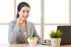 Jeune femme d'affaires asiatique appréciant une salade saine Image libre de droits