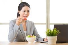 Jeune femme d'affaires asiatique appréciant une salade saine Photographie stock