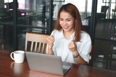 Jeune femme d'affaires asiatique gaie avec l'ordinateur portable souriant sur le lieu de travail dans le bureau Concept réussi d' Images libres de droits