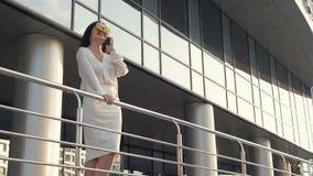 Jeune femme d'affaires attirante dans la chemise blanche et le costume noir descendant la rue le long de la main courante contre banque de vidéos