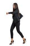 Jeune femme d'affaires attirante dans le fonctionnement de costume tout en vérifiant le temps sur sa montre Image libre de droits