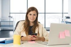 Jeune femme d'affaires attirante de portrait d'entreprise à la mise en réseau de bureau au téléphone portable Photographie stock libre de droits