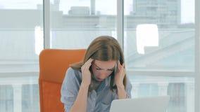 Jeune femme d'affaires attirante semblant fatiguée ayant le mal de tête dans le bureau clips vidéos