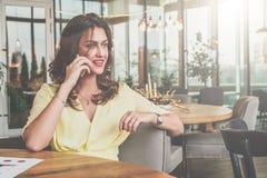 Jeune femme d'affaires attirante seul s'asseyant à la table en café et appelant par le téléphone portable Photo stock