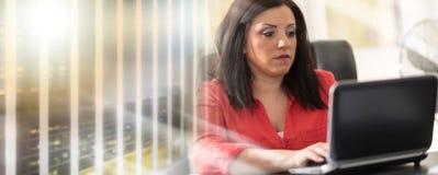 Jeune femme d'affaires attirante travaillant sur l'ordinateur portable, effet de la lumière ; photo stock