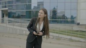 Jeune femme d'affaires avec de longs cheveux utilisant l'équipement formel attendant la cabine d'uber et regardant autour après u banque de vidéos