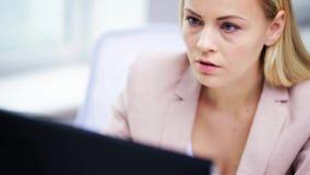 Jeune femme d'affaires avec l'ordinateur dactylographiant au bureau banque de vidéos