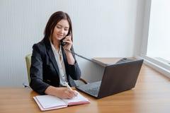 Jeune femme d'affaires avec l'ordinateur portable parlant au téléphone dans le bureau photos stock