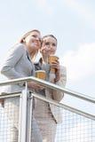 Jeune femme d'affaires avec la tasse de café jetable se dirigeant tout en se tenant avec le collègue à côté de la clôture contre  Photos stock