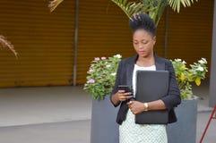Jeune femme d'affaires avec un ordinateur portable et un téléphone portable photographie stock libre de droits