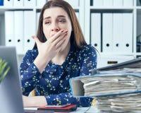 Jeune femme d'affaires baîllant à un bureau moderne devant l'ordinateur portable, couvrant sa bouche Femme surchargé Photo stock