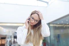 Jeune femme d'affaires blonde appelant tandis qu'inquiétude dans le cente d'affaires image stock