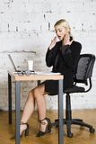 Jeune femme d'affaires blonde de beauté s'asseyant à une table de bureau avec l'ordinateur portable, le carnet et les verres dans Photo stock