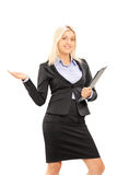 Jeune femme d'affaires blonde tenant un presse-papiers et faisant des gestes avec Images libres de droits