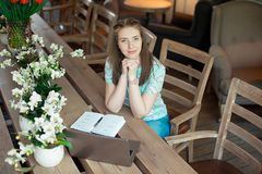 Jeune femme d'affaires caucasienne en café se reposant à la table avec le regard fixe réfléchi photographie stock libre de droits