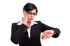 Jeune femme d'affaires contrôlant sa montre-bracelet Photographie stock