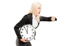 Jeune femme d'affaires courant tard avec une horloge murale dans sa main Photos stock