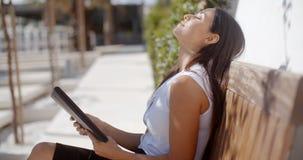 Jeune femme d'affaires détendant sur un banc extérieur photo stock