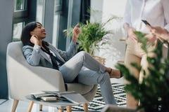 Jeune femme d'affaires d'afro-américain se reposant dans la chaise et le sourire images libres de droits
