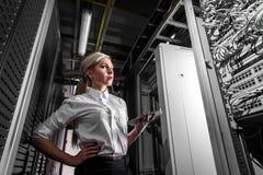 Jeune femme d'affaires d'ingénieur dans la chambre de serveur Image stock
