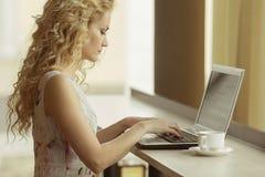 Jeune femme d'affaires dans la robe se reposant à la table en café, regardant sur l'écran de l'ordinateur portable photographie stock
