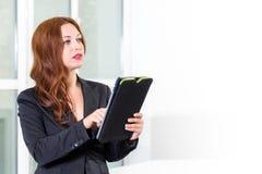 Jeune femme d'affaires dans le bureau lumineux moderne tenant le comprimé avec une liste de tâches L'espace libre pour le texte B Photos libres de droits
