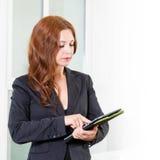 Jeune femme d'affaires dans le bureau lumineux moderne tenant le comprimé avec une liste de tâches L'espace libre pour le texte B Images stock