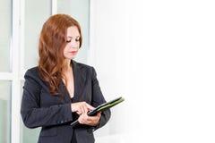 Jeune femme d'affaires dans le bureau lumineux moderne tenant le comprimé avec une liste de tâches L'espace libre pour le texte B Photos stock