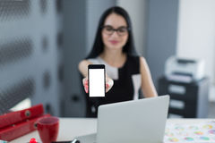 Jeune femme d'affaires dans le bureau tenant un smartphone et un sourire image libre de droits