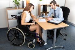 Jeune femme d'affaires dans le fonctionnement de fauteuil roulant avec un collègue masculin au bureau images stock