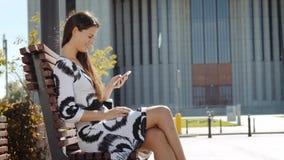 Jeune femme d'affaires dans une robe se reposant sur un banc avec un téléphone à disposition et des travaux clips vidéos