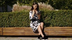 Jeune femme d'affaires dans une robe se reposant sur un banc et des travaux sur un comprimé banque de vidéos