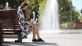 Jeune femme d'affaires dans une robe se reposant sur un banc et des travaux sur l'ordinateur banque de vidéos