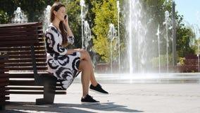 Jeune femme d'affaires dans une robe se reposant sur un banc et parlant au téléphone banque de vidéos