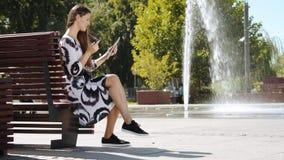Jeune femme d'affaires dans une robe se reposant sur un banc et parlant sur le comprimé banque de vidéos