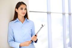 Jeune femme d'affaires de brune ou fille d'étudiant regardant l'appareil-photo Photos libres de droits