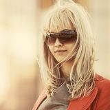 Jeune femme d'affaires de mode dans des lunettes de soleil marchant sur la rue de ville photo stock