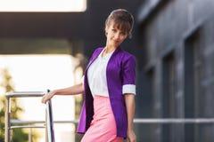 Jeune femme d'affaires de mode dans le blazer pourpre marchant dans la rue de ville Images stock