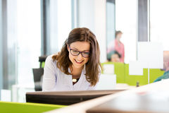 Jeune femme d'affaires de sourire à l'aide de l'ordinateur dans le bureau Photographie stock libre de droits