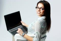 Jeune femme d'affaires de sourire à l'aide de l'ordinateur portable Photographie stock