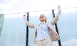 Jeune femme d'affaires de sourire au-dessus de l'immeuble de bureaux Photographie stock libre de droits
