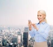 Jeune femme d'affaires de sourire avec le smartphone Photographie stock libre de droits