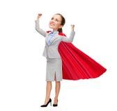 Jeune femme d'affaires de sourire dans le cap rouge de super héros Photo stock
