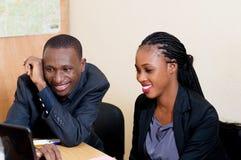 Jeune femme d'affaires de sourire partageant un ordinateur portable avec son collègue Photo libre de droits