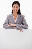 Jeune femme d'affaires de sourire se penchant sur le mur vide Images libres de droits