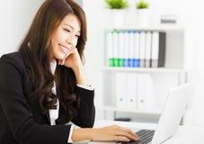 Jeune femme d'affaires de sourire travaillant avec l'ordinateur portable Image stock